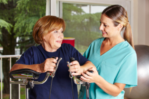 caregiver assisting old woman to exercise